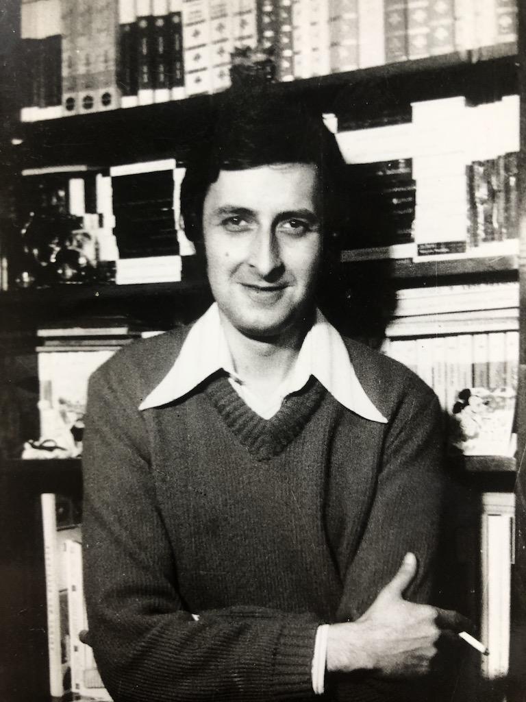 Tata, fotografiat in fata unui corp de bibliotca de acasa